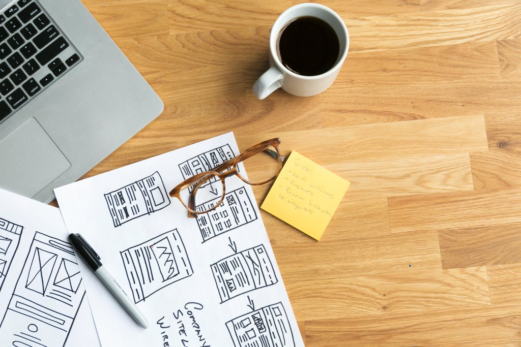 designers desk with coffee wireframes